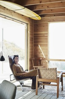 Kate sits in the living room, which is outfitted with vintage Eames and Jens Risom chairs.
