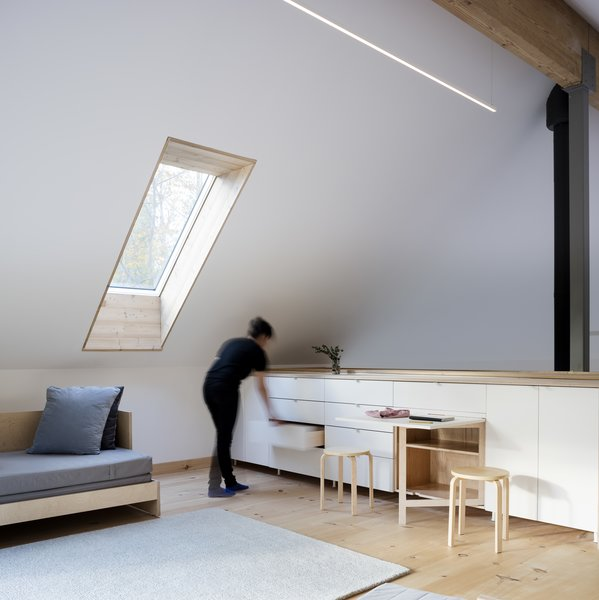 The loft floors are made of white pine recycled from a tree on the property. Todd and Maria designed and fabricated the sitting room's daybed as well as the table that swings out from the CabParts prefab Catskills Watershed House cabinetry; the stools are from IKEA.