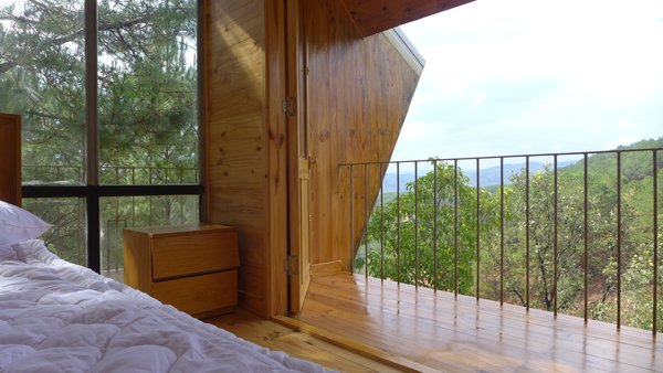 Balconies along the side of each cabin overlook expansive mountainous views.