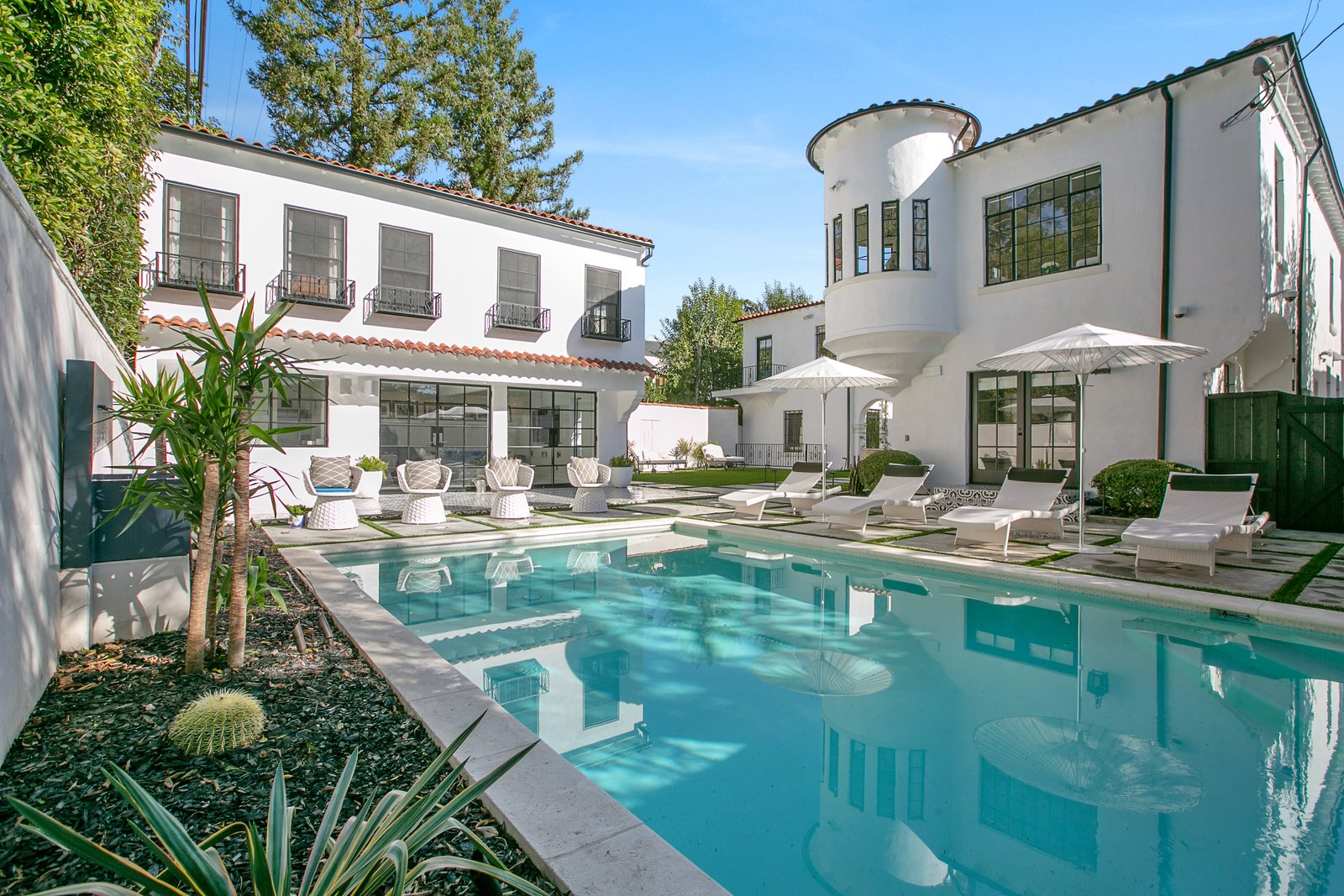 Outdoor, Trees, Concrete Fences, Wall, Pavers Patio, Porch, Deck, Shrubs, Back Yard, Raised Planters, and Large Pools, Tubs, Shower Near the pool is a detached guesthouse, which features a kitchen, dining area, and living room.  Photo 3 of 14 in Beck's Former Mediterranean-Style Retreat Lists For $8M