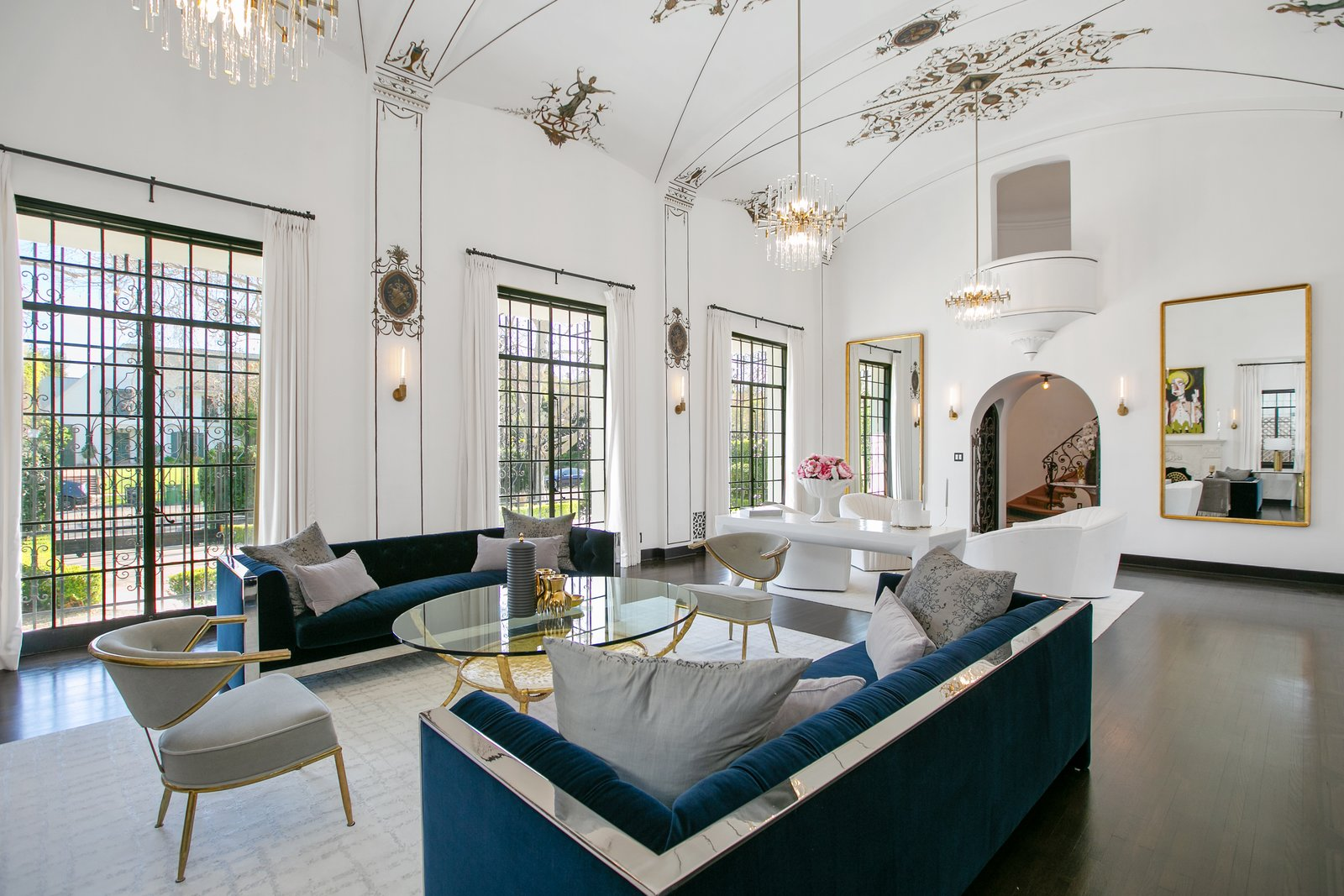 Living Room, Dark Hardwood Floor, Table, Sofa, Coffee Tables, Chair, Ceiling Lighting, Wall Lighting, and Rug Floor Full of chandeliers, the expansive living room also features hand-painted ceilings.  Photo 5 of 14 in Beck's Former Mediterranean-Style Retreat Lists For $8M