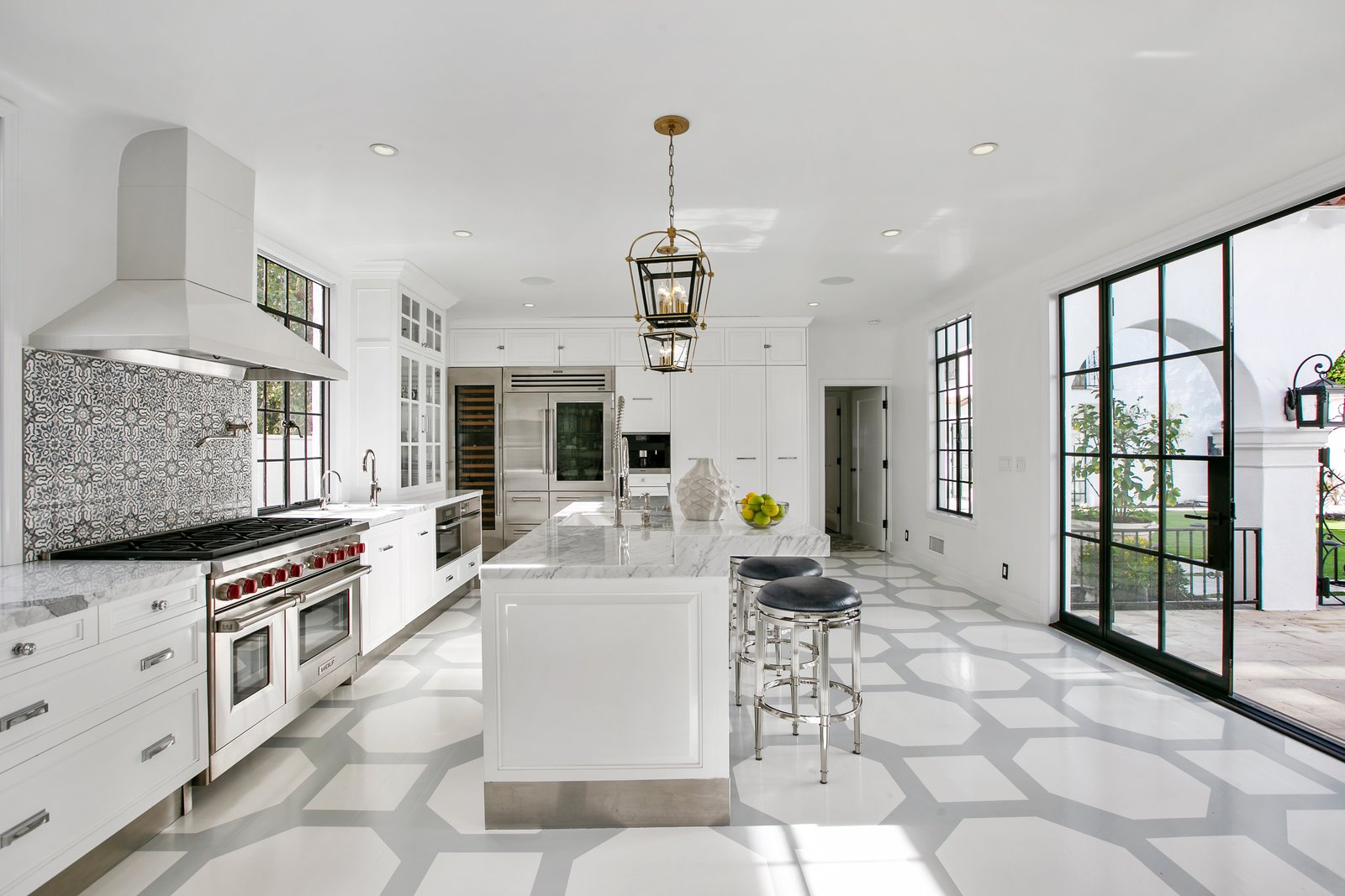 Kitchen, Vinyl, White, Ceramic Tile, Range, Drop In, Mosaic Tile, Granite, Refrigerator, Dishwasher, Ceiling, Recessed, and Range Hood The bright and airy kitchen is comprised of Miele and Sub-Zero appliances.  Kitchen Vinyl Dishwasher Drop In Photos from Beck's Former Mediterranean-Style Retreat Lists For $8M