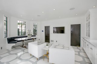 Along with a plush banquette, the whitewashed kitchen also features hand-painted floors.