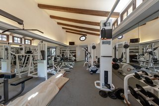 Exposed wooden beams continue into the estate's well-equipped gym.