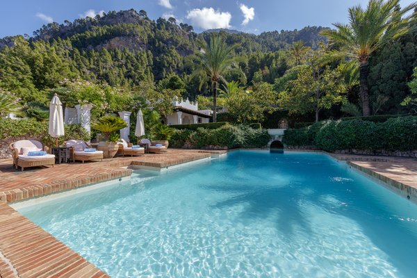 A closer look at the marble-lined swimming pool, which is also surrounded by lush greenery.