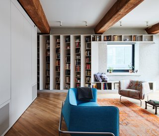 To elegantly showcase the couple's extensive book collection without cluttering the 1,100-square-foot home, the New York–based firm has created a custom library via angled shelving.