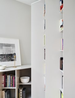 The staggered shelves define the space, wrapping around the perimeter of the home while appearing as a series of columns that project outwards at an angle.