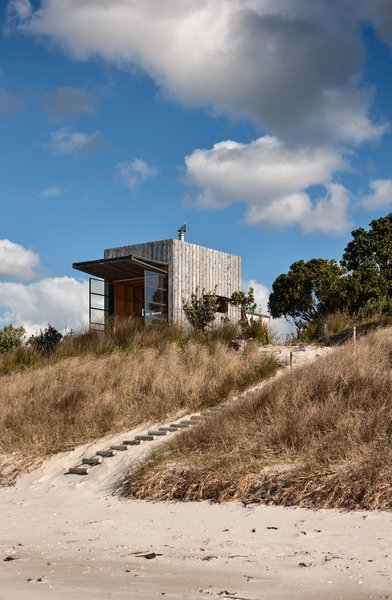 Perched quietly on the dunes of New Zealand's Coromandel Peninsula, Hut on Sleds serves as a small, sustainable beach retreat for a family of five.