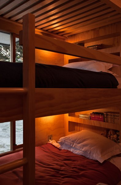 Within the hut, the architects have utilized every inch of available space, including incorporating secret cubby holes into the children's bunkbeds.