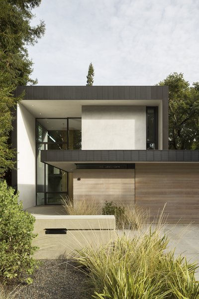 Clad in zinc, stucco, cedar, and glass, Tree House by Aidlin Darling Design is a slender, two-story home composed of interlocking rectangular volumes, and fronted with a low-lying garage.