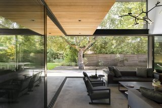 The 5,870-square-foot home gracefully stretches in a linear fashion from the front to the back of the lot. It rests atop a concrete plinth—a response to the site's high water table.