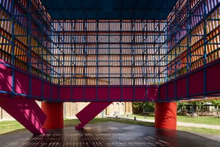 "Inside, the ""backstage"" area of the cube reveals a bright blue, wooden space-frame. Guests are invited to climb up the pink pair of processional staircases, where they can then wind through the structure, gazing upon the mesmerizing intersection of battens and wires."