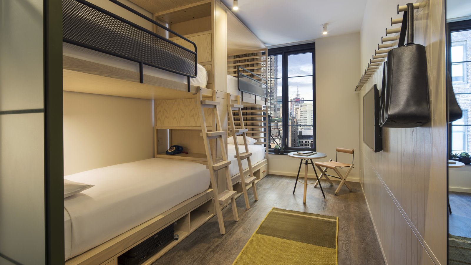 """Bedroom, Medium Hardwood Floor, Storage, Ceiling Lighting, Chair, Rug Floor, and Bed The bunk rooms exhibit the same attention to detail. """"There's a huge benefit to bringing luxury hotel designers like Yabu Pushelberg to an affordable hotel project,"""" says Hochberg. """"It's not just about creating an efficient space that looks good. What you end up with is a room with personality and character. It's a room that tells a story.""""  Photos from This Micro-Room Hotel in New York's Flower Market Channels a Decadent Garden of Eden"""