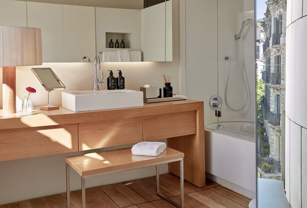 White finishes meet light wood in the stylish bathrooms.