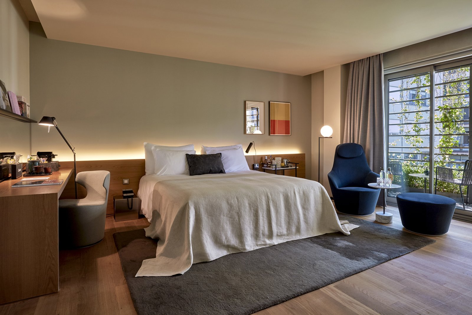 Bedroom, Bed, Night Stands, Table, Floor, Shelves, and Medium Hardwood The accommodations vary in size and layout—this room faces an interior courtyard.  Bedroom Medium Hardwood Floor Photos from Barcelona's Hottest New Hotel Draws Inspiration From a Rebellious Female Author