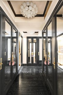A black-trimmed entrance hall lined with mirrored closets sets an elegant tone.