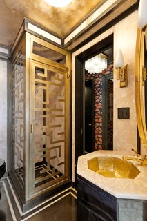 The guest bath features onyx and marble finishes, along with a custom shower and sink.