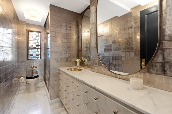 The expanded master bath features glass tiles by Ann Sacks and Waterworks fixtures.