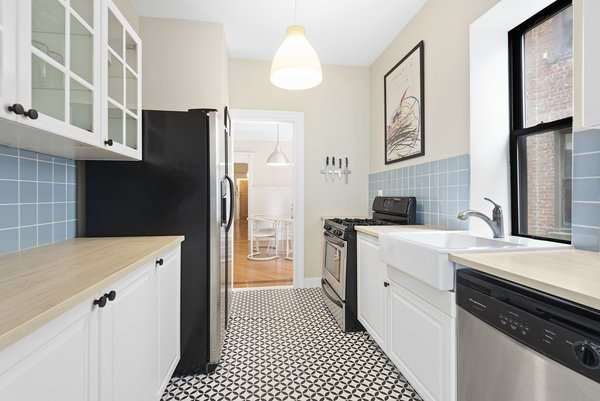 Recently remodeled, the light-filled kitchen features stainless-steel appliances, black-and-white tiled flooring, as well as plenty of storage.
