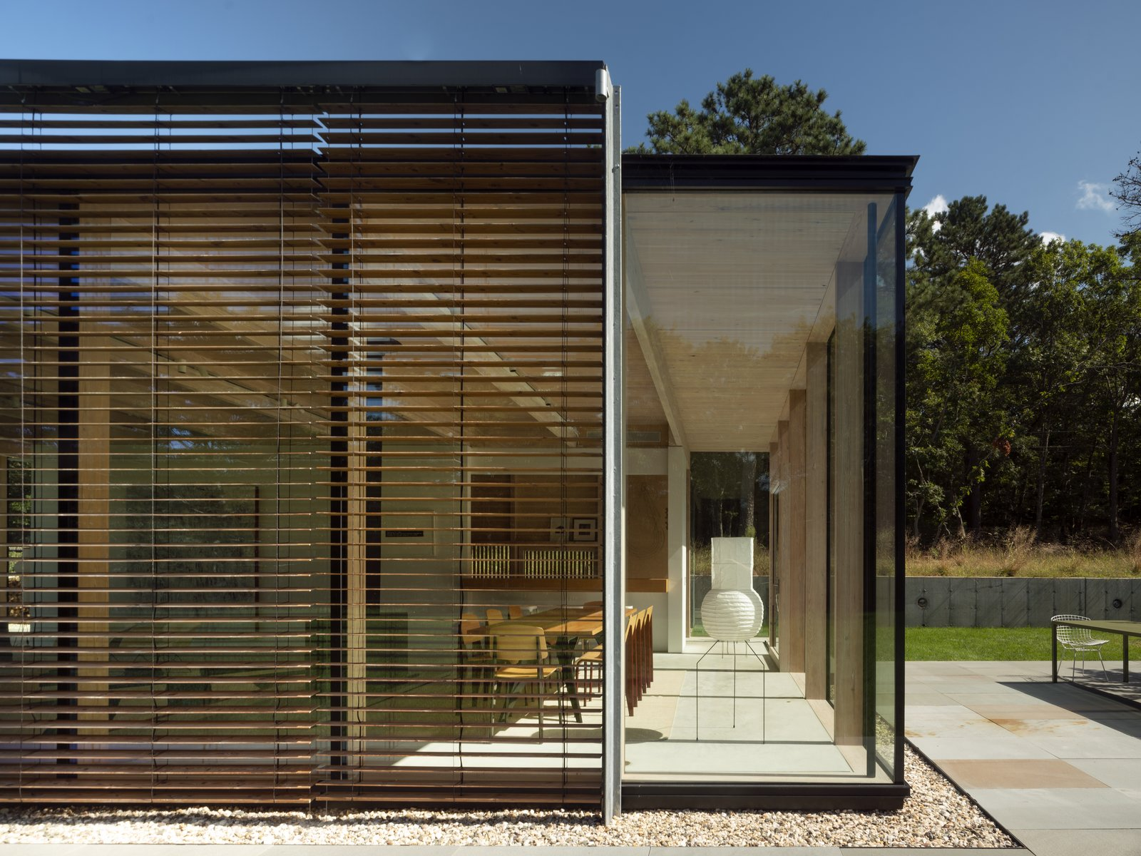 "Exterior, Glass Siding Material, House Building Type, Wood Siding Material, and Flat RoofLine Stretching across 2,500 square feet, the holiday home has been configured using a series of ""dematerialized  Best Photos from An Energy-Efficient Glass House in East Hampton Shifts With the Seasons"