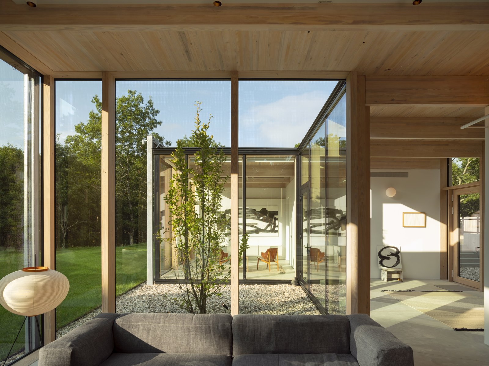 Living, Concrete, and Sofa Clad in textured timber, the interior ceilings allow the structural material to speak for itself, while also providing a warm contrast to the minimal design.  Best Living Photos from An Energy-Efficient Glass House in East Hampton Shifts With the Seasons