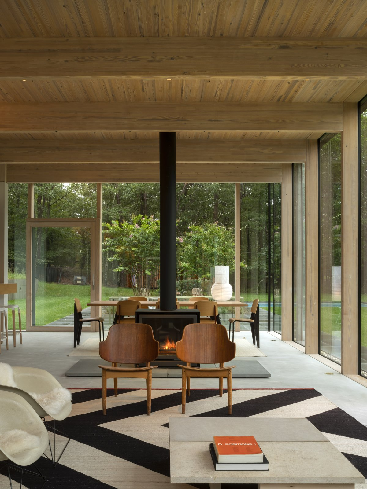 Living, Two-Sided, Chair, and Coffee Tables A slender, black double-sided fireplace distinguishes the living room from the dining area.  Living Two-Sided Photos from An Energy-Efficient Glass House in East Hampton Shifts With the Seasons