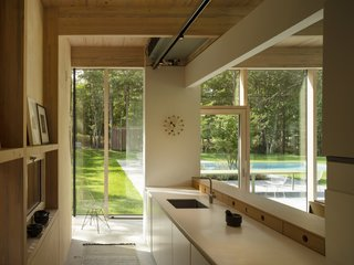 Wood finishes continue into the light-filled kitchen, which is just steps away from the pool.