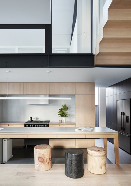 An abstracted take on the kitchen island design gives the impression of a table when viewed from the living area, integrating both rooms around a central gathering point.