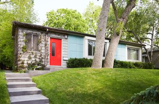 "Sitting alongside five other Lustron homes on Nicollet Avenue in Minneapolis, this rare prefab is cladded in sleek, ""surf-blue"" steel panels. A bright red door welcomes guests inside."