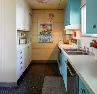 In the kitchen, blue cabinets add another burst of color.