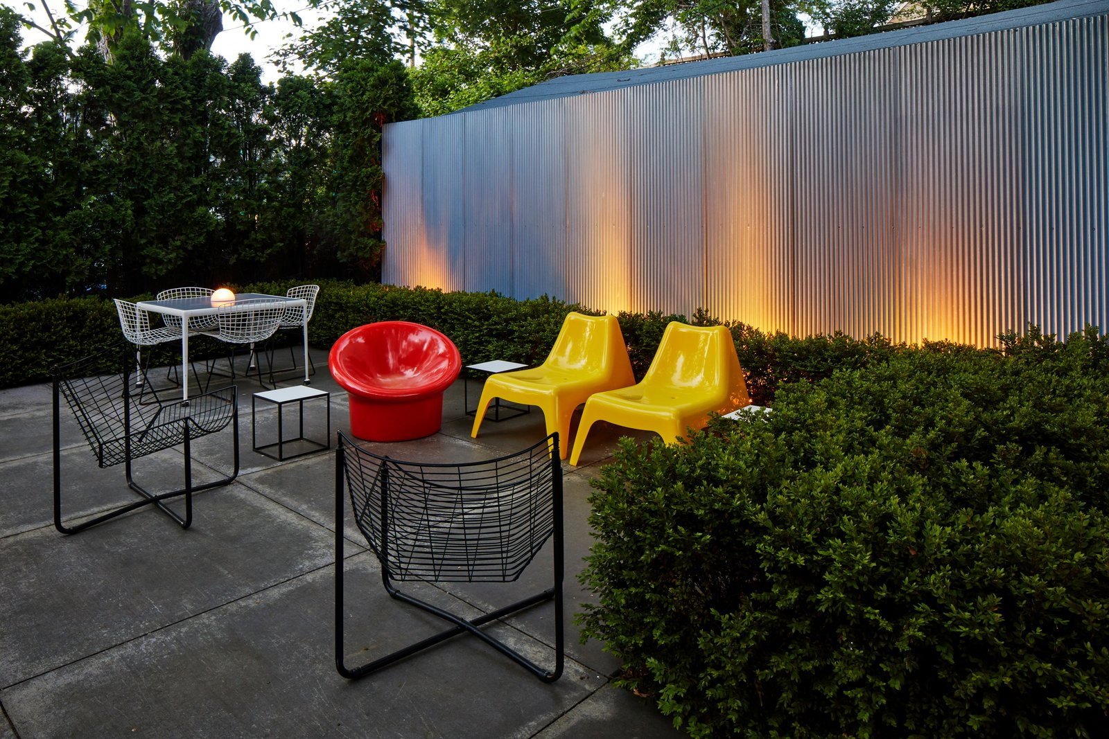 Outdoor, Metal, Concrete, Landscape, Garden, Shrubs, and Vertical With ample seating and an illuminated landscape, the backyard can facilitate easy entertaining.  Outdoor Metal Shrubs Garden Photos from A Lustron Steel Prefab in Pristine Condition Lists For $350K