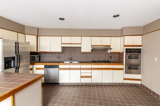 The spacious kitchen comes with all new appliances, including two built-in wall ovens.