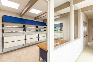 A large home office with an abundance of storage is located on the second level.