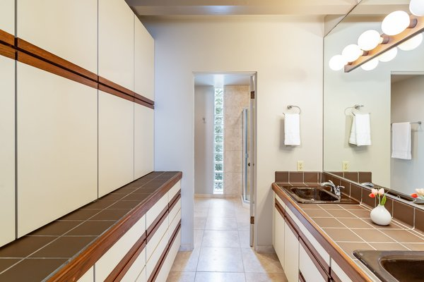 The master bath includes floor-to-ceiling cabinetry along one wall for ample storage.