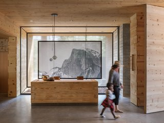 In the reception area, Geremia Design called upon Chambers Art & Design to co-design and engineer a stretched fabric screen depicting Yosemite's Half Dome. The pendant lighting is by Workstead.