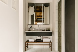 The bathroom and vanity area balance a sparse aesthetic with luxurious finishes.