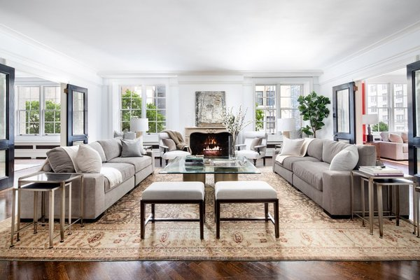 Just off the foyer is a luxe living room, which is anchored by expansive windows and a delicately carved wood-burning fireplace. The spacious area is flanked by a corner library and dining room, creating a seamless flow of open space.