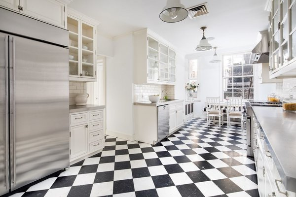 Featuring a timeless black-and-white marble checkerboard floor, the eat-in kitchen receives an abundance of natural light thanks to its huge, six-over-six pane sash window.