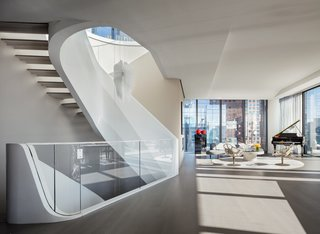 Designed inside and out by Zaha Hadid, the penthouse features the famed architect's signature curves throughout. Each level is united by a sculptural white staircase.