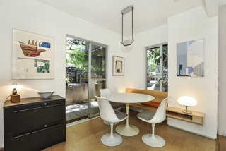The quaint eating area located off the kitchen has direct access to a serene lower-level patio.
