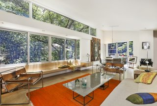 The bright and airy living room overlooks the verdant backyard, providing tree house-like vibes.