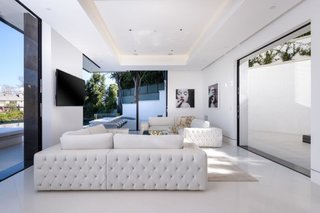 Dressed in all white, the corner living room offers ample seating while framing stunning views.