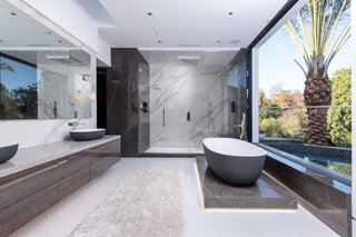 An expansive picture window ushers ample natural light and fresh air into the master bath.