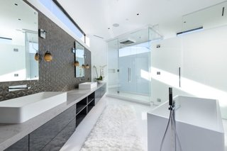 Another one of the home's five bathrooms. Horizontal windows brighten the room from above.