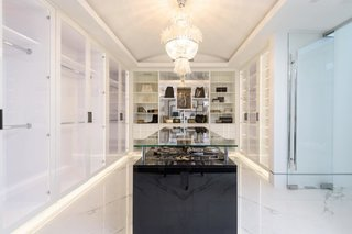 A glamorous walk-in closet is fitted with marble floors and custom-built cabinetry and shelving.
