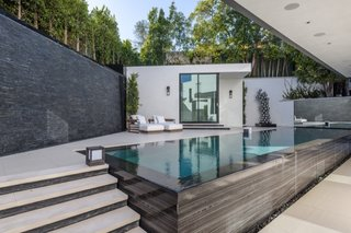 Surrounded by lush greenery, the impressive backyard area is peacefully secluded.