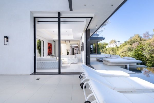 Floor-to-ceiling sliding doors unite the living room with one of the property's two pool areas.  Photo 3 of 14 in Actress Bette Davis's Former Beverly Hills Home Serves Up Hollywood Glam For $34.5M