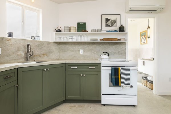 The kitchen's dark green cabinets contrast nicely with the home's bright white color palette.
