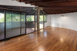 A dramatic wood-beamed sunburst ceiling takes center stage in the living room. Large sliding doors lead to a spacious open-air terrace, complete with views of the San Fernando Valley.