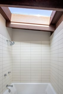 A large skylight above the shower ushers in ample natural light into the bathroom.